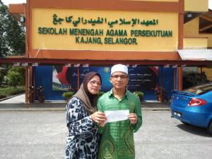 Ahmad Hasbullah bersama ibu tersayang sedang menunjukkan slip peperiksaan yang menunjukkan keputusan yang cemerlang