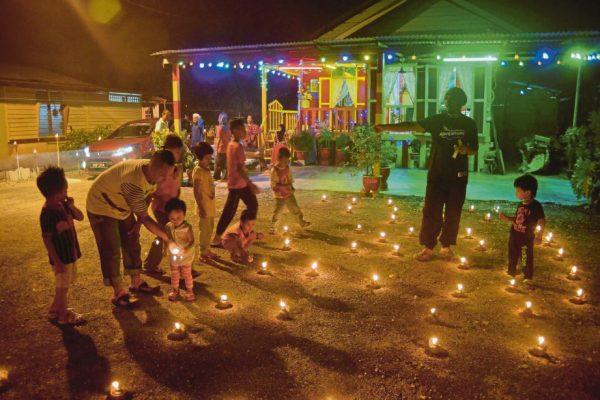 KLANG 04 JULY 2016. Kanak-kanak kelihatan seronok melihat lebih 150 pelita raya yang dipasang oleh Ramli Bandi, 64, di sekitar halaman rumahnya di Jalan Sungai Udang, Klang bagi memeriahkan sambutan Hari Raya Aidilfitri pada malam tujuh likur atau 10 malam terakhir Ramadan. STR/FAIZ ANUAR